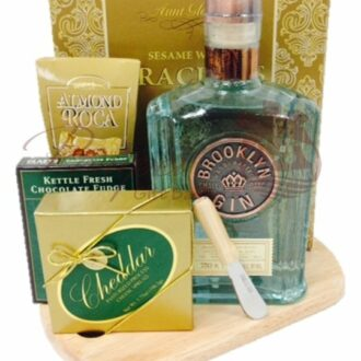 The Boss' Favorite Gin Gift Basket holds a bottle of Brooklyn Gin, cheese spread, crackers, and chocolates on a wooden cutting board